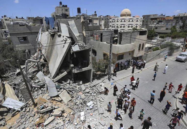 Palestinos observan los daños a una casa destruida por un misil israelí, en Rafah, sur de la Franja de Gaza. (Agencias)