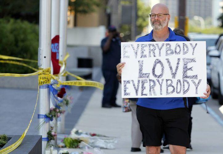 Chris Bailey camina junto a un altar improvisado en la calle Griffin de Dallas, Texas, con un cartel que dice 'Todos, amen a todos'. (Agencias)