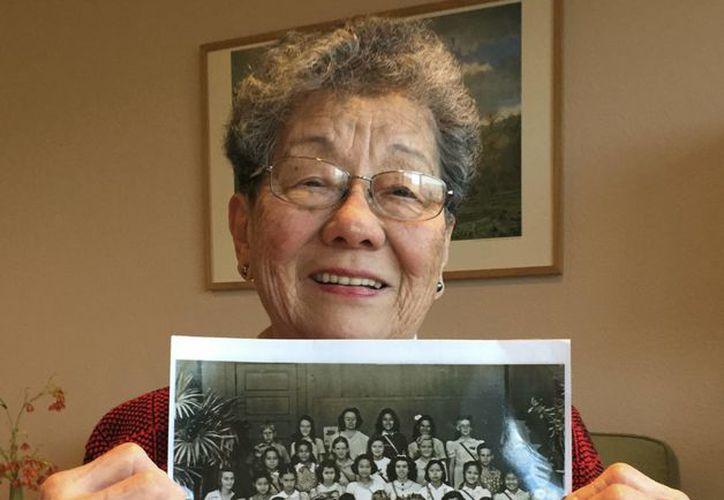 Florence Seto muestra una foto con sus compañeras del quinto grado de la primaria en una escuela de Honolulu, tomada poco después del ataque japonés a Pearl Harbor el 7 de diciembre de 1941. Seto es la tercera desde la izquierda en la primera fila. (AP Photo/Gillian Flaccus)