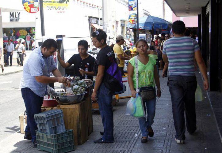 Los ambulantes obligan a los peatones a bajarse a la cinta asfáltica. (Christian Ayala/SIPSE)
