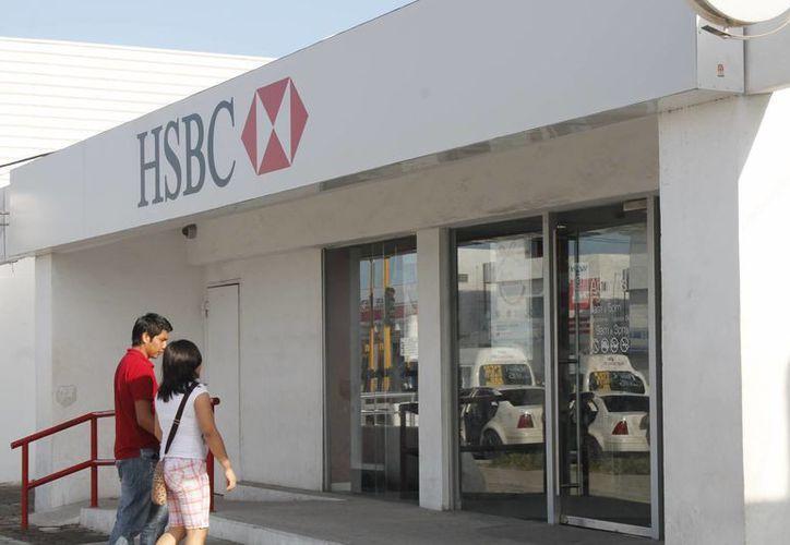 """Familiares de clientes fallecidos pueden buscar la información en los bancos e incluso en la Condusef, para """"rastrear"""" estos recursos. En la imagen, un par de personas entran a una sucursal de una institución bancaria. (Archivo/SIPSE)"""