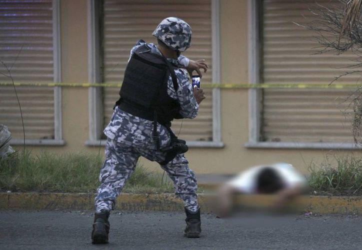 Una de las víctimas de los disturbios de Veracruz es fotografiado por un elemento de la Marina. (AP/Felix Marquez)