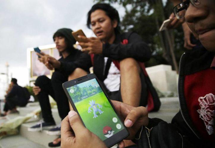 En esta imagen, un hombre indonesio muestra su smartphone mientras juega a 'Pokemon Go' en Yakarta, Indonesia. (AP Foto/Tatan Syuflana)