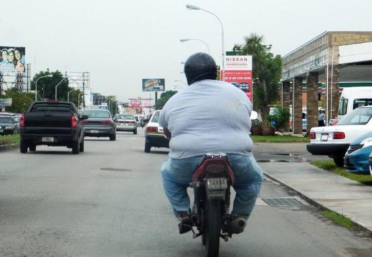 Indican que la obesidad es un factor de riesgo para padecer diabetes e hipertensión. Imagen de una persona con sobrepeso conduciendo una motocicleta en calles de la ciudad. (Milenio Novedades)