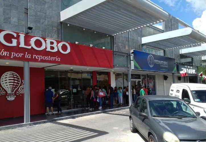 La gente comenzó a hacer fila poco antes del mediodía de este viernes para probar el pan tradicional de El Globo. Las puertas se abrieron en punto de las 12:00 horas. (SIPSE.com)