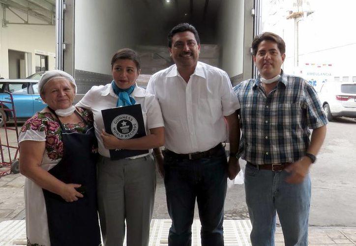 La maestra cocinera Miriam Peraza Rivero, con la representante del Guiness Record y funcionarios. (SIPSE)