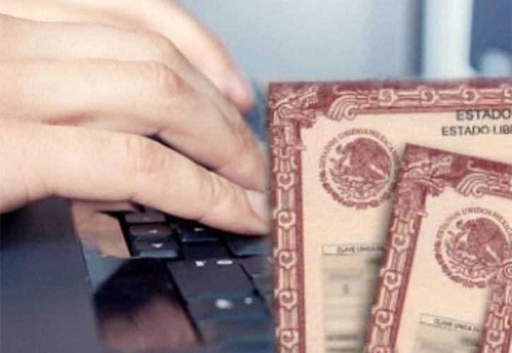 Ahora los mexicanos podrán tramitar documentos como actas de nacimiento, matrículas consulares y pasaportes desde cualquier consulado de México, en el mundo. Archivo de contexto de una persona tecleando y un acta de nacimiento. (Archivo/Notimex)