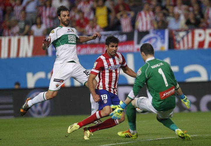 Diego Costa (c) anotó el segundo gol en el encuentro ante Elche para el líder Atlético, que continúa como único invicto en su estadio e hilvanó su octava victoria consecutiva. (AP)