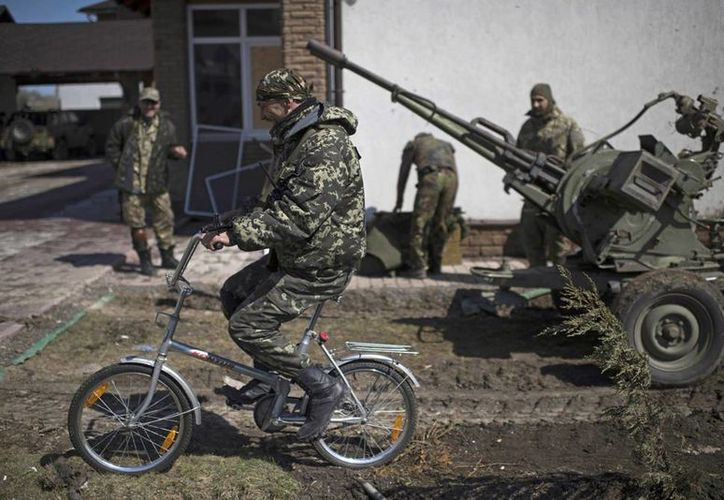 Un militar ucraniano monta una bicicleta en Shyrokyne, este de Ucrania. Unos 900 soldados serán entrenados por estadounidenses. (Foto AP/Evgeniy Maloletka)