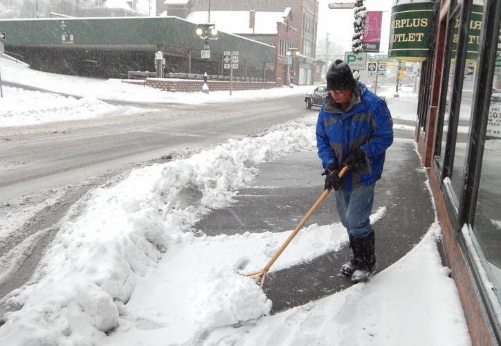 Un hombre retira la nieva de una banqueta en el centro de Houghton, Michigan. (Agencias)