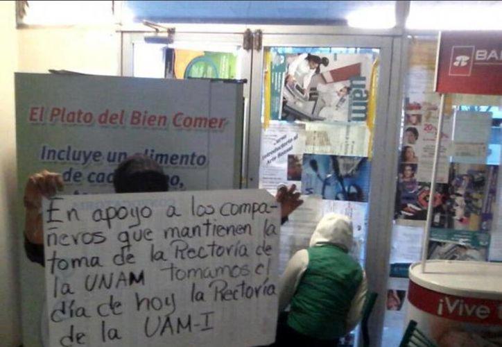 Desde adentro de rectoría, activistas de la UAM Iztapalapa muestran imagen de la toma. (Milenio)
