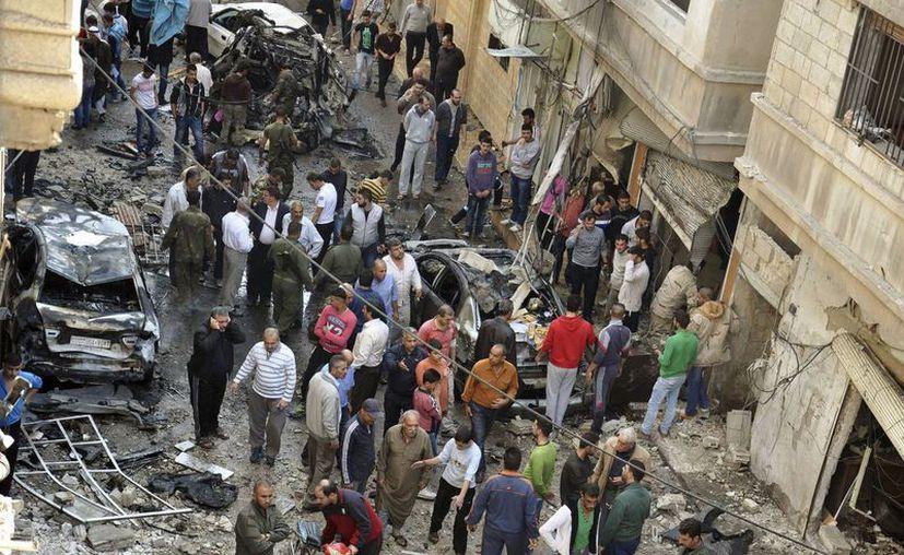 Policías y ciudadanos sirios observan los escombros que dejó un atentado suicida con un coche bomba contra una zona de mayoría alauí, a la que pertenece el presidente sirio, Bachar al Asad. (Archivo/EFE)