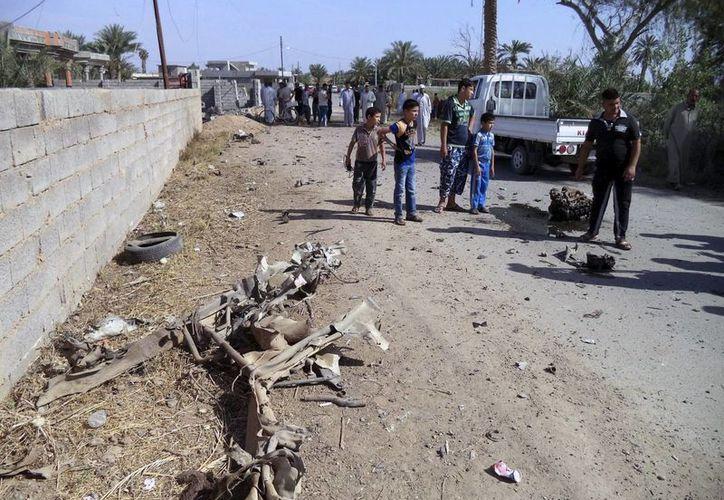 Varios curiosos congregados junto al lugar donde explotó hace dos días un coche bomba en Tikrit, Irak. (EFE/Archivo)