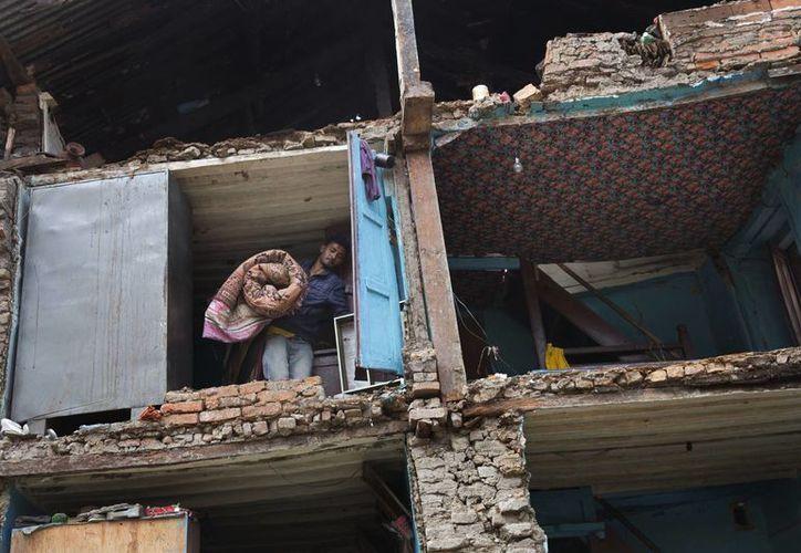 Un residente lleva sus pertenencias recuperadas de las ruinas de su casa tras el terremoto del sábado en Bhaktapur, Nepal. (Foto AP / Bernat Armangue)