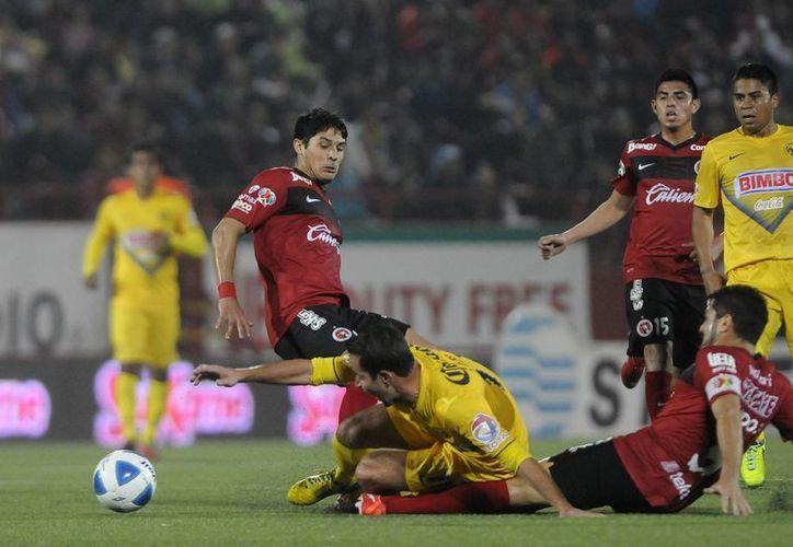 Los Xolos de Tijuana <i>mordieron</i> durante casi todo el partido a las Aguilas, En la gráfica, Javier Gandolfi  se barre para evitar que Luis Gabriel Rey se lleve el balón. (Notimex)