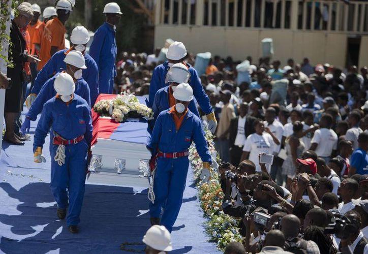 Socorristas lleban un féretro con los restos de una de las 17 víctimas de un accidente en el carnaval de Haití en el funeral público en Puerto Príncipe. (Agencias)