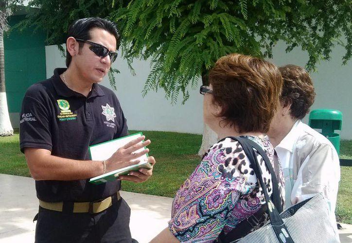 Un agente de la SSP auxilia a las dos turistas de Baja California que fueron víctimas de un engaño telefónico de extorsionadores. (SIPSE)