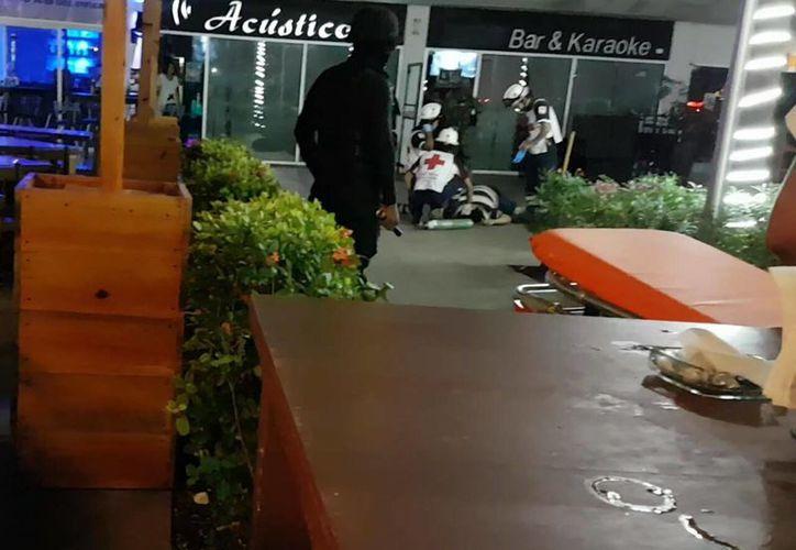 Un hombre yace muerto afuera de un bar de Plaza Solare, la madrugada de este domingo. (Inspector Nocturno/SIPSE)