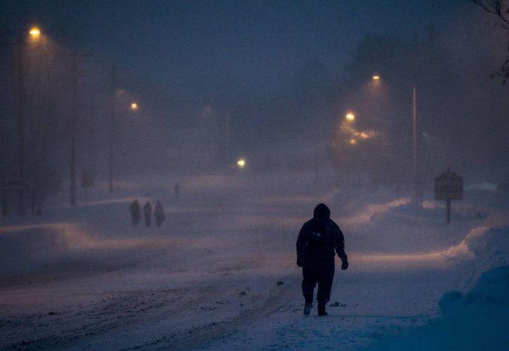 La nieve sepulta gran parte de Estados Unidos. En al menos 10 estados ya se declaró estado de emergencia, además de que ya se registraron por lo menos 18 decesos. En la foto, un vecino de Harrisonburg camina hacia su destino, ante la imposibilidad de usar su vehículo. (AP)