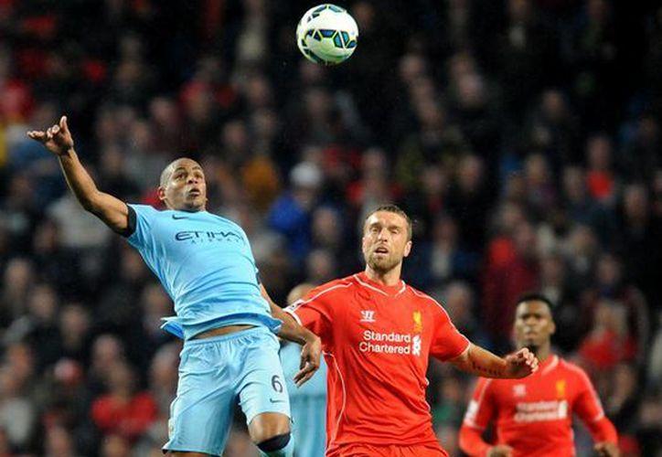 Fernando, del Manchester City (i) y Ricky Lambert, del Liverpool, disputan la pelota en la segunda jornada de la Liga Premier. (Fotos: AP)