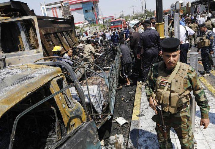 Las fuerzas de seguridad iraquíes inspeccionan el escenario de un ataque suicida con coche bomba en Basora, la segunda ciudad más grande de Irak. (Agencias)