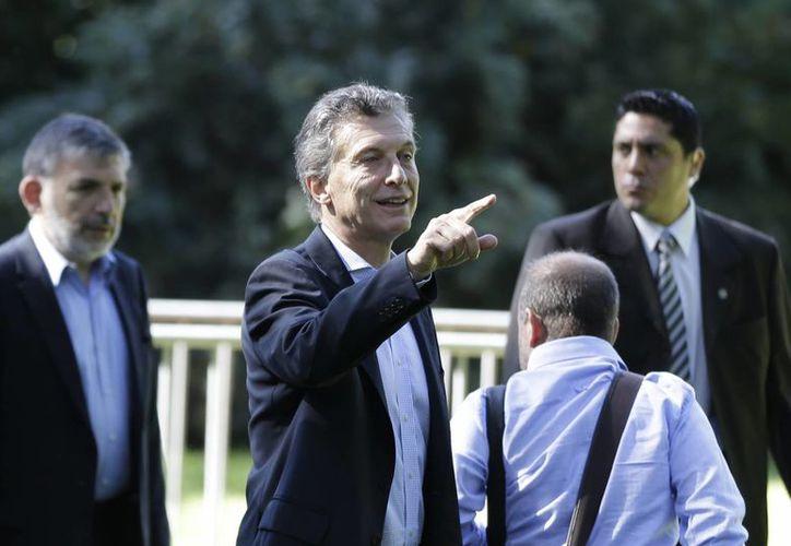 El presidente electo de Argentina Mauricio Macri señala al llegar a la presentación de su gabinete en el jardín botánico de Buenos Aires. (Agencias)