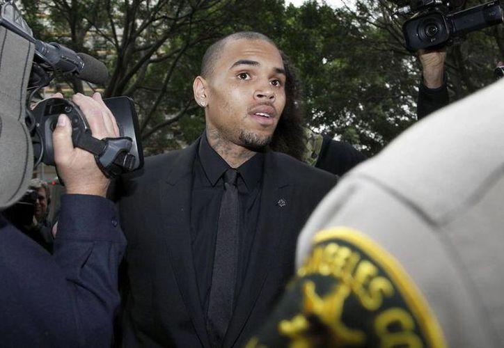 Brown y su guardaespaldas fueron arrestados el mes pasado acusados de golpear a un hombre que trató de meterse a una fotografía que le tomaban al cantante. (Agencias)