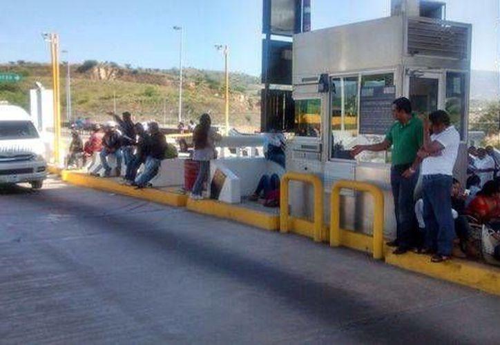 En vez de permitir el cobro del peaje, maestros de la CNTE en Oaxaca realizaron labores de boteo y volanteo. (Milenio)