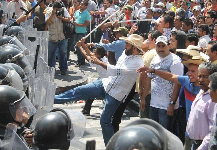 Imagen de archivo de un enfrentamiento entre integrantes de la CNTE y agentes en Morelia, Michoacán. (Archivo/Notimex)