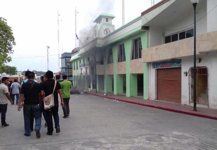 Durante los disturbios un grupo de personas causó vandalismo y quemó la presidencia municipal de Palenque. (twitter.com/GabyCoutino)