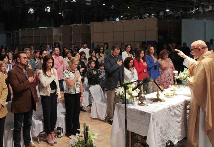 Los actores y personal de producción de la telenovela 'A que no me dejas', durante la misa previo al comienzo del programa. (Notimex)