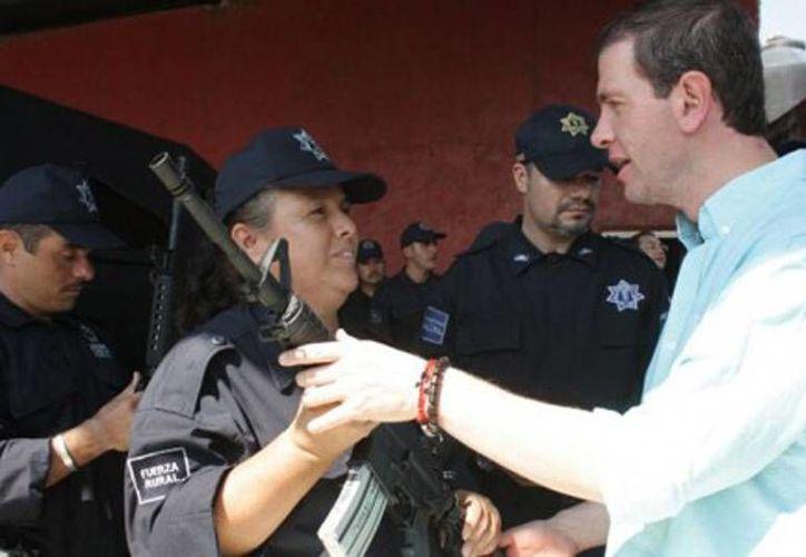 Juana Reyes (en la imagen con el comisionado Alfredo Castillo) asegura que aunque hay fotografías en las que aparece con el uniforme de la Fuerza Rural, su registro fue un error. (quadratin.com.mx)