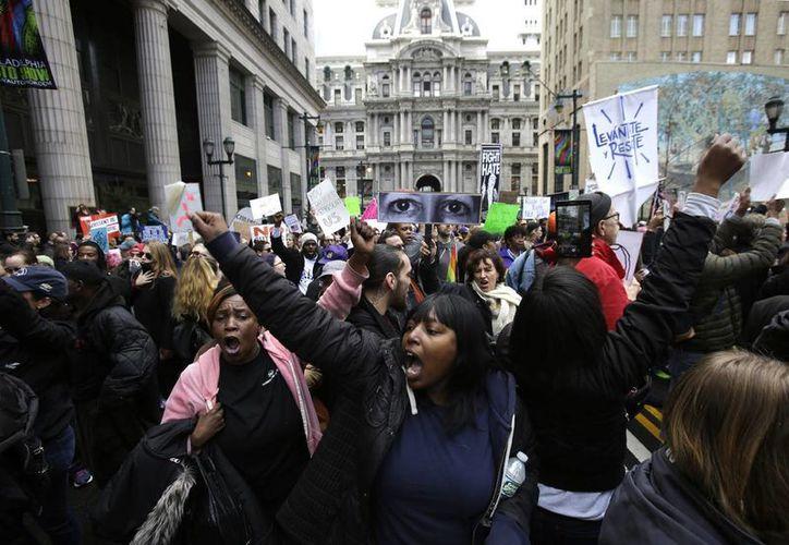 Cientos de manifestantes marcharon en el centro de Filadelfia en protesta por la visita del presidente Donald Trump este jueves. Varios altos funcionarios federales han sido despedidos por la nueva administración como parte de su esfuerzo para 'limpiar la casa'. (Foto AP / Jacqueline Larma)