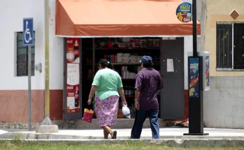 Los pequeños negocios abarroteros tienen hasta el próximo 31 para inscribirse al programa 'Intelitiendas Kokay', Imagen de dos personas que caminan cerca de un tendejón popular. (Milenio Novedades)