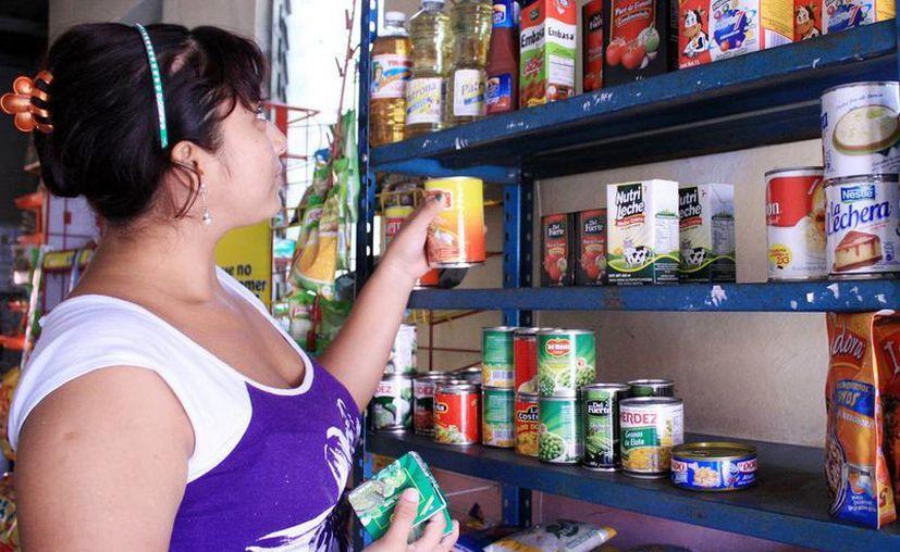 Las tienditas de la esquina se preparan para homologar imagen. Imagen de una mujer que acomoda productos en un pequeño establecimiento. (Milenio Novedades)