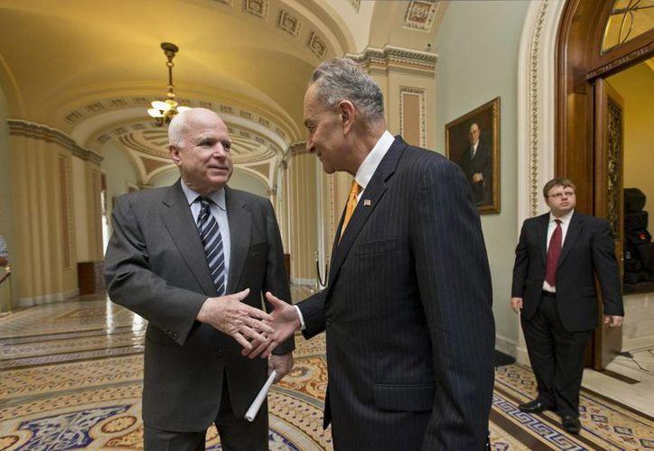 El senador republicano por Arizona John McCain (izq) y el senador demócrata por Nueva York Charles Schumer se estrechan la mano en el Capitolio en Washington. (Agencias)