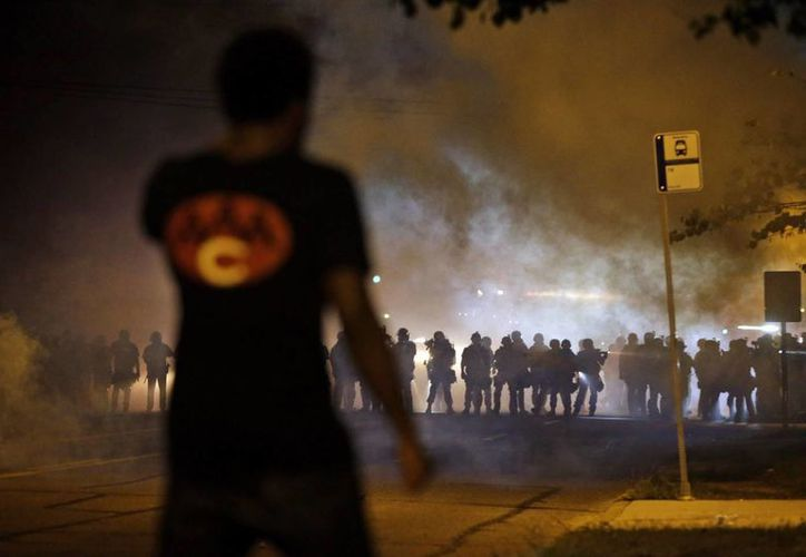Un hombre observa a la policía, a través de una nube de humo, en un enfrentamiento contra manifestantes en el suburbio de St. Louis. (Agencias)