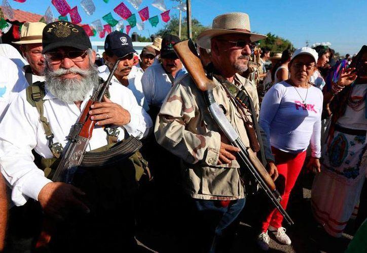 Hipólito Mora (al centro, de sombrero), líder de las autodefensas de La Ruana, estaba acusado de homicidio y privación ilegal de la libertad. (Efe/Archivo)