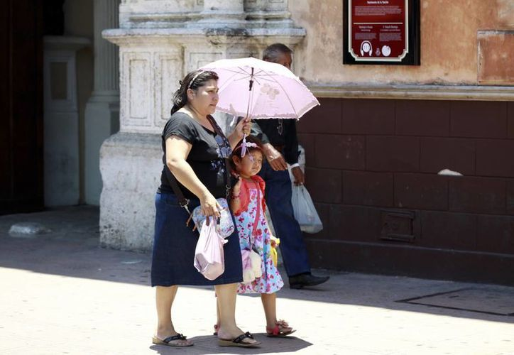 Fue común ver a las personas con sombrillas para protegerse del sol. (Chrsitian Ayala/SIPSE)