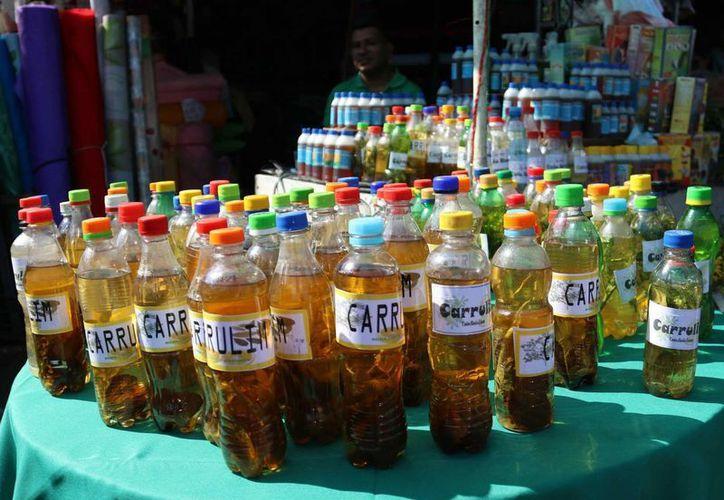 Vendedores de hierbas medicinales del Mercado 4 de Asunción, Paraguay, ofrecen al público el popular 'carrulim', un antídoto contra los efectos del caluroso viento norte de agosto en el que se mezcla la ruda y la ortiga con la caña de azúcar. (EFE)