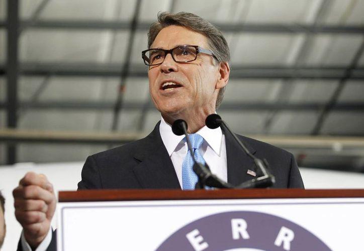 Rick Perry lanzó su campaña hoy desde el hangar del aeropuerto Addison, de Dallas, decorado con un avión militar de carga C-130 que voló durante sus años en la Fuerza Aérea. (AP)