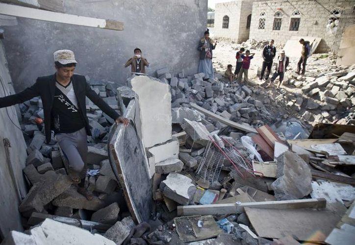 Un muchacho busca algo que pueda ser de utilidad, entre escombros de un edificio derribado por bombardeos cerca del aeropuerto de Saná, capital de Yemen. (Foto AP)