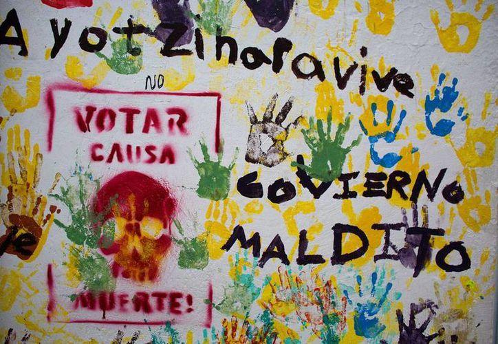 Según el INE, las condiciones se están dando para la instalación de las casillas electorales en Oaxaca. La imagen es de un cartel de protesta contra el proceso electoral, en Tixtla, Guerrero, y está utilizada como contexto. (AP)
