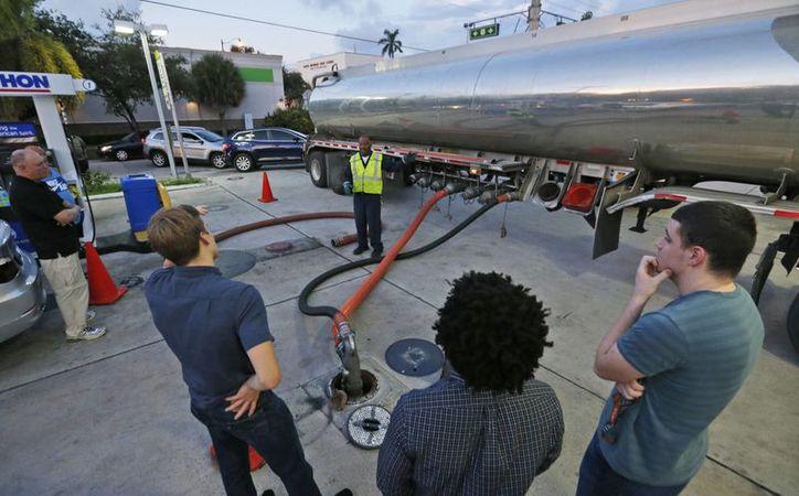 Varios conductores miran mientras Wayne Demps, de CWC Transportation, en el centro al fondo, llena los tanques vacíos de una gasolinera de Marathon, en Hollywood, Florida. (AP/Wilfredo Lee)