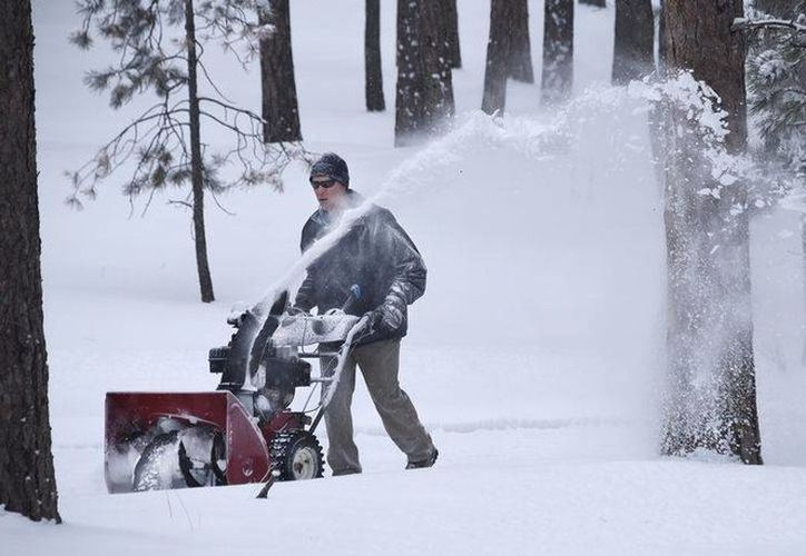 Un hombre despeja nieve frente a su casa junto a la carretera 105 cerca de Sierra Way al nordeste de Colorado Springs en Colorado. (Agencias)