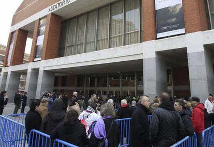 Admiradores de Paco de Lucía cuando comenzaban a hacer cola en las vallas instaladas a la entrada del Audietorio Nacional de Madrid donde se instaló la capilla ardiente del guitarrista. (EFE)
