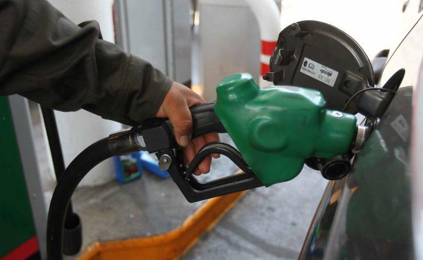 En el primer semestre de 2015 la Profeco realizó mil 290 acciones de verificación a estaciones. Imagen de un empleado que despacha gasolina. (Archivo/Notimex)