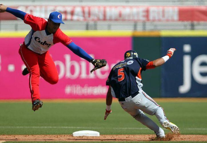 El shortstop cubano Luis A. Valdes (i) falla en su intento de ponchar al venezolano Orlando Arcia en la segunda base en partido de la penúltima jornada de la Serie del Caribe. (Foto: AP)