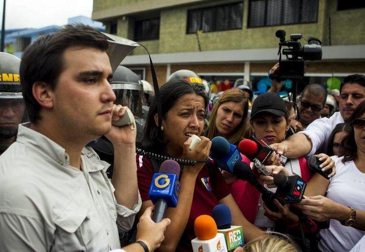 """Gaby Arellano (c), dirigente estudiantil de la Universidad de Los Andes, habla a los medios junto a Juan Pablo Lopez Activista de Voluntad Popular (izq), acompañada de un grupo de estudiantes y simpatizantes del partido político """"Voluntad Popular"""" en Caracas, Venezuela. (EFE)"""