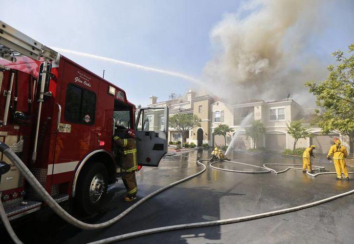 Bomberos vierten agua en un complejo de condominios que fue alcanzado por el incendio. (Agencias)